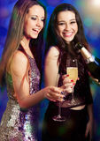 Two beautiful girl friends with champagne at party. Two beautiful girls friends with champagne being served by a waiter at party or disco. Light effects Stock Photo
