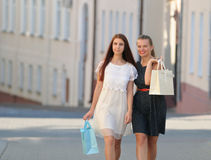 Two beautiful girl-friends in dresses holding shopping bags in t. Heir hands on the promenade Stock Images