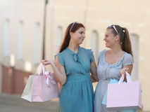 Two beautiful girl-friends in dresses holding shopping bags in their hands on the walk. Happy Shopping Stock Image