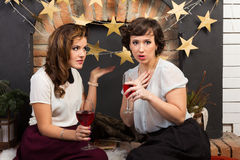 Two beautiful girl friends by the fireplace. Drinking wine Stock Photos