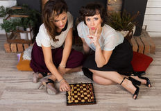Two beautiful girl friends by the fireplace. Two beautiful girl friends playing chess by the fireplace Stock Photos