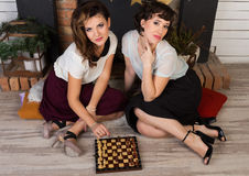 Two beautiful girl friends by the fireplace. Two beautiful girl friends playing chess by the fireplace Stock Images