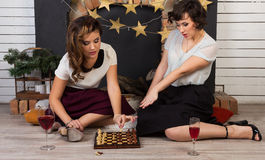 Two beautiful girl friends by the fireplace. Two beautiful girl friends playing chess by the fireplace Royalty Free Stock Photography