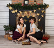 Two beautiful girl friends by the fireplace. Two beautiful girl friends playing chess by the fireplace Stock Photo