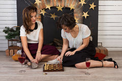 Two beautiful girl friends by the fireplace. Two beautiful girl friends playing chess by the fireplace Stock Image