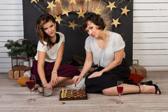 Two beautiful girl friends by the fireplace. Two beautiful girl friends playing chess by the fireplace Royalty Free Stock Image