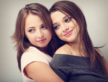 Two beautiful girl friends looking with love and natural tendern. Ess emotion on blue background. Toned closeup portrait Royalty Free Stock Images
