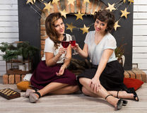 Two beautiful girl friends. Playing chess by the fireplace Royalty Free Stock Photography