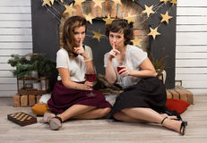 Two beautiful girl friends sharing secrets. By the fireplace Royalty Free Stock Image
