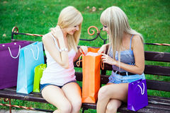 Two beautiful girl friends with shopping bags. In a park Stock Photo
