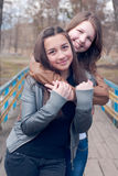 Two beautiful girl friends smiling on the bridge. Two beautiful girl friends smiling and hugging on the bridge outdoor Royalty Free Stock Image