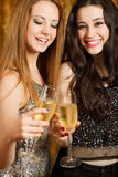 Two beautiful girl friends toasting with champagne. At party Stock Photography