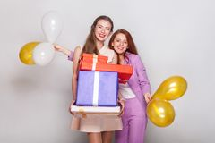 Two beautiful girl holding  gifts box and air balloon have a hap Stock Photos