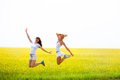 Two beautiful girl jumps the yellow flowers. Two beautiful girl in white clothes jumps the yellow flowers Stock Photo