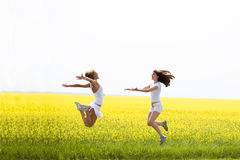 Two beautiful girl jumps yellow flowers Royalty Free Stock Image