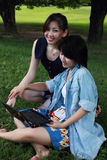Two beautiful girl on a laptop computer outdoors. Two beautiful girl with a laptop computer outdoors. Lay on the green grass Stock Photos