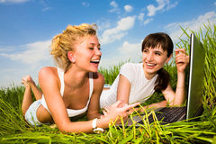 Two beautiful girl on a laptop computer outdoors. Two beautiful girl in white clothes on a laptop computer outdoors. Lay on the green grass Royalty Free Stock Images
