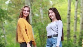 Two beautiful girl with long hair plush in nature. Two beautiful young women friends flap their long luxurious hair in the park summer day stock video