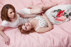 Two beautiful girl on a pink blanket. Stock Photos