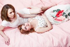 Two beautiful girl on a pink blanket. Royalty Free Stock Photography