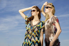 Two beautiful girl in sunglasses on background blue sky Royalty Free Stock Photo