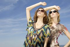 Two beautiful girl in sunglasses on blue sky Royalty Free Stock Photos