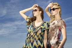 Two beautiful girl in sunglasses on blue sky Royalty Free Stock Photography