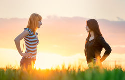 Two beautiful girl in the sunset having an argue in the nature. Two beautiful girl in the sunset having an argue Royalty Free Stock Photos