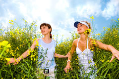 Two beautiful girl in white go to yellow flowers. Two beautiful girl in white clothes go to the yellow flowers. Against the backdrop of blue sky Stock Images