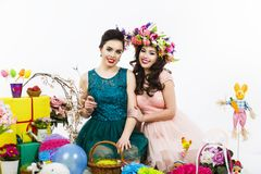 Two beautiful girlfriend girls, basket with eggs and flower deco Royalty Free Stock Image
