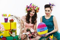 Two beautiful girlfriend girls, basket with eggs and flower deco Royalty Free Stock Photo