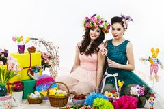 Two beautiful girlfriend girls, basket with eggs and flower deco Stock Photography