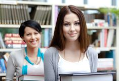 Two beautiful girlfriends carry books Royalty Free Stock Image