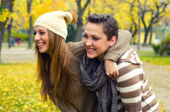 Two beautiful girlfriends having fun in the autumn park Royalty Free Stock Photo