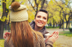 Two beautiful girlfriends having fun in the park on colorful aut Stock Photography