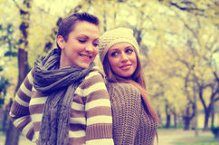 Two beautiful girlfriends having fun in the park on colorful aut Royalty Free Stock Photos