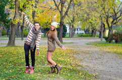 Two beautiful girlfriends having fun in the park on colorful aut Stock Image