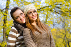 Two beautiful girlfriends having fun in the park on colorful aut Stock Photo