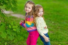 Two beautiful girlfriends posing in the garden Royalty Free Stock Photos