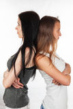 Two beautiful girlfriends of resentment and quarrel. On a white background Royalty Free Stock Photography