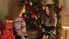 Two beautiful girlfriends sit by the Christmas tree. Talking and giving gifts stock video footage