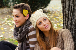 Two beautiful girlfriends sitting in the park on colorful autumn Royalty Free Stock Image
