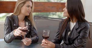 Two beautiful girlfriends sitting on terrace. Drinking red wine and chatting with each other stock video