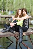 Two beautiful girls. Two beautiful embracing girls on a mooring Royalty Free Stock Photos