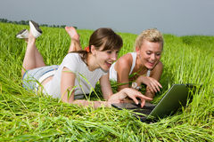 Two beautiful girls. In white clothes are laughing near laptop computer outdoors. Lay on the green grass Stock Images