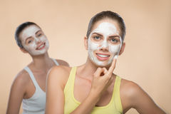 Two beautiful girls applying facial cream mask and Stock Photos