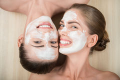 Two beautiful girls applying facial cream mask and. Portrait of two beautiful girls with facial cream on their  faces looking at the camera and lying face to Royalty Free Stock Image