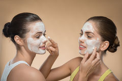 Two beautiful girls applying facial cream mask and Royalty Free Stock Image