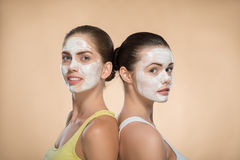 Two beautiful girls applying facial cream mask and Stock Photo