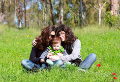 Two beautiful girls with a baby Stock Image